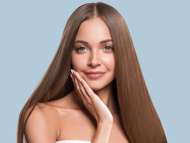 아름 다운 긴 부드러운 머리 여자 행복 깨끗 한 피부 얼굴 색 배경. 파란색