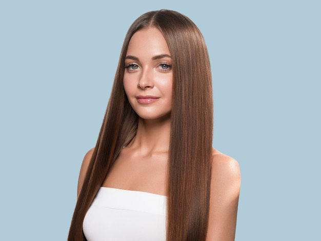 Beautiful long smooth hair woman happy clean skin face color background. blue