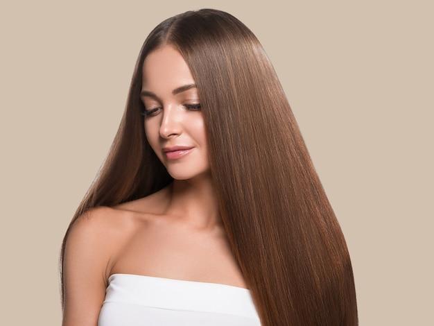 Красивые длинные гладкие волосы женщины счастливы чистой кожи лица цвет фона. коричневый.