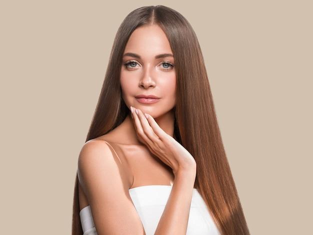 아름 다운 긴 부드러운 머리 여자 행복 깨끗 한 피부 얼굴 색 배경. 갈색.