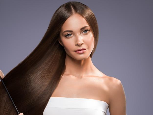 아름 다운 긴 부드러운 머리 여자 행복 깨끗 한 피부 얼굴 색 배경. 보라색.
