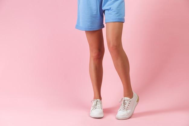 スタジオファッションでポーズをとるショートパンツと白いスニーカーの美しい長い女性の脚。