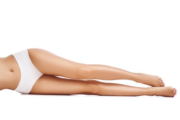 白い背景、コピースペース、クローズアップの美しい長い女性の脚。女性は白い下着を着ています