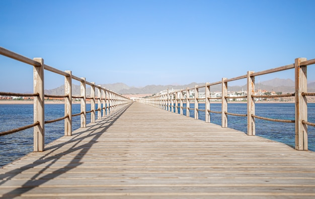 Beautiful long wooden pier among the ocean and mountains.