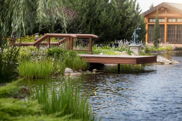 Красивый длинный деревянный пирс на пруду роскошного особняка