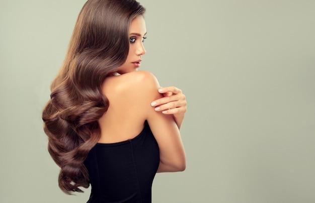 長く濃い巻き毛のヘアスタイルと鮮やかなメイクの美しい見た目のモデル完璧な濃いウェーブのかかった光沢のある髪プロファイルのポートレート理髪アートヘアケアと美容製品