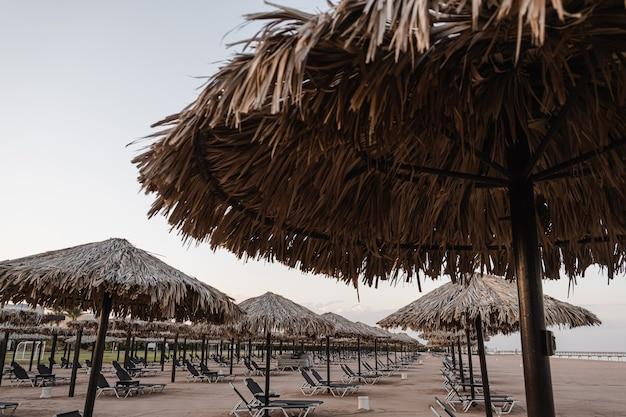 아름다운 라운지 파빌리온 캐노피는 모래와 바다의 측면과 푸른 하늘이있는 해변에서 휴식을 취합니다.