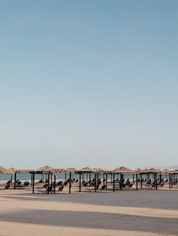 바다 쪽 전망과 푸른 하늘이있는 해변에서 휴식을 취할 수있는 아름다운 라운지 파빌리온 캐노피