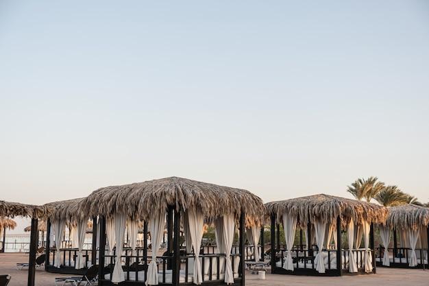 모래와 바다의 측면과 푸른 하늘이있는 해변에서 휴식을 취할 수있는 아름다운 라운지 파빌리온