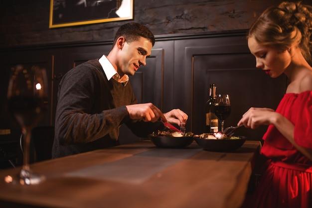 レストランで食べる美しい愛のカップル、ロマンチックな夜。赤いドレスを着たエレガントな女性と彼女の男性は一緒に余暇