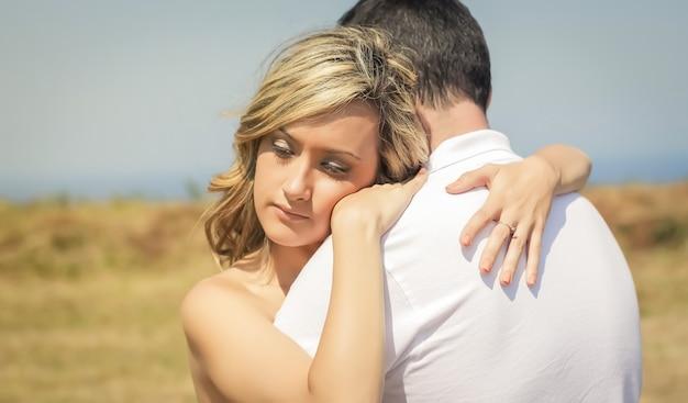 Красивая любовная пара, обнимая на открытом воздухе в летний день на фоне природы