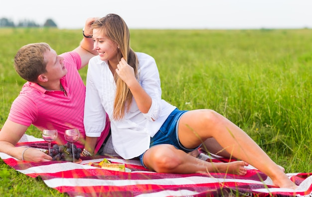 Beautiful love couple having romantic picnic outdoors on summer sunny day.