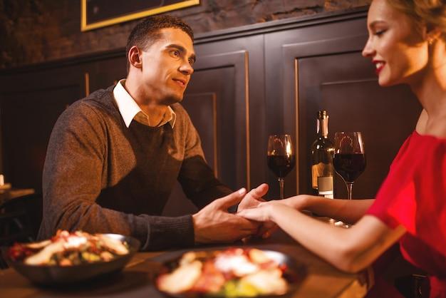 レストランでロマンチックな夜の美しい愛のカップル。赤いドレスと彼女の男がテーブル、記念日のお祝いに座っているエレガントな女性