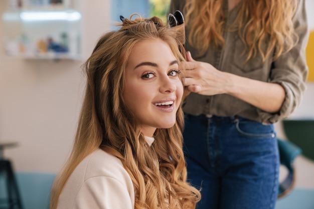 Красивая милая блондинка с длинными волосами, сидя в салоне красоты, вьющиеся волосы