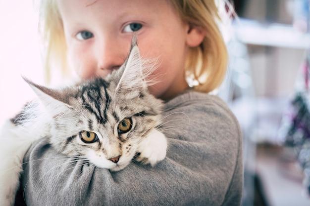 Defocused 장면에서 어린 아이의 아름다운 사랑스러운 초상화와 카메라를보고 그에 귀여운 고양이 고양이