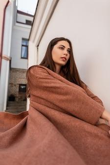 아름 다운 사랑스러운 꽤 젊은 세련 된 여자 패션 모델은 도시의 빈티지 건물 근처 유행 봄 코트에서 회전하고 있습니다. 매력적인 섹시 우아한 유행 소녀 캐주얼 옷 야외에서 포즈.