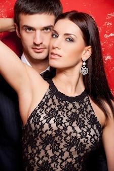 美しい愛情のあるカップル。赤い背景に対してポーズをとって美しい若い身なりのよいカップル