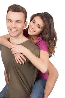 아름다운 사랑의 커플. 쾌활한 젊은 사랑의 커플 포옹과 흰색 절연 서있는 동안 카메라에 미소