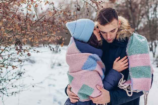 Beautiful loving couple walking and hugging in winter forest. people warming covered with blanket