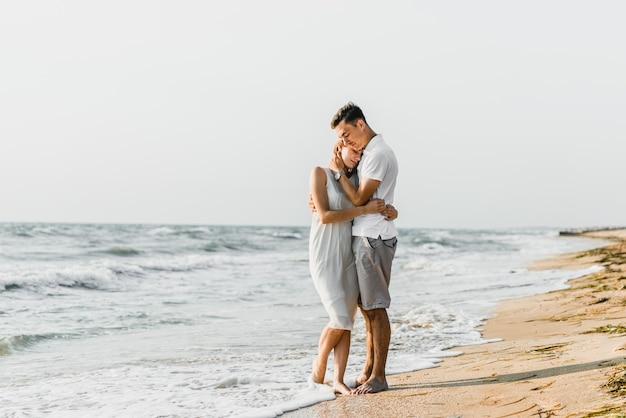 美しい愛情のあるカップルが海岸を歩きます。幸せな若いカップルはビーチで時間を過ごします。新婚旅行の新婚夫婦。その日の夜明けに女の子と男。休暇中のカップル。夏休み。カップルハグ