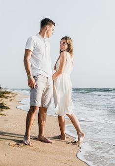 美しい愛情のあるカップルが海岸を歩きます。幸せな若いカップルはビーチで時間を過ごします。