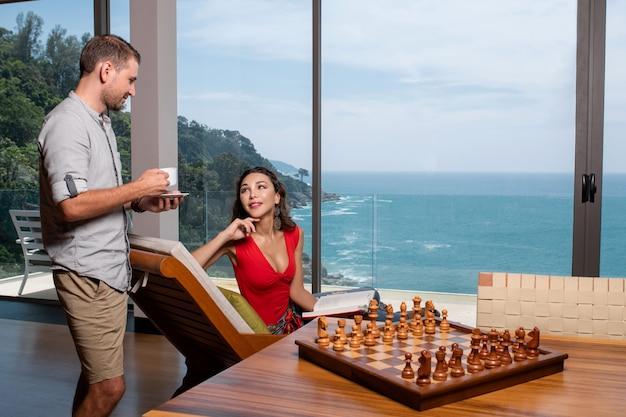 Красивая любящая девушка смотрит на своего парня. пара отдыхает на вилле с великолепным видом на море. красивые интерьеры с шахматной доской