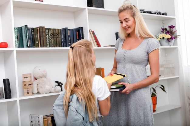 Beautiful, loving mother gives her daughter a book