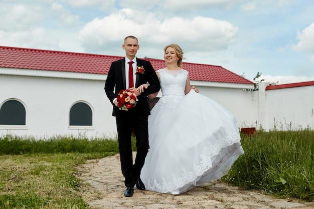 Красивая влюбленная свадебная пара регистрирует брак и гуляет по красивой набережной. счастья и любви