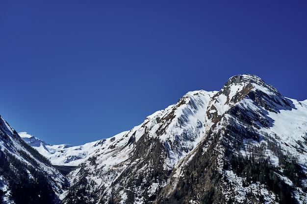 Beautiful low angle shot of a mountain with snow covering the peak and the sky in the background