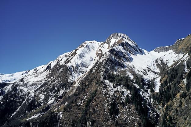 Bello colpo di angolo basso di una montagna con neve che copre il picco e il cielo in