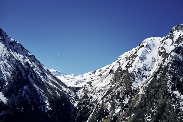 Bella inquadratura dal basso delle montagne innevate e del cielo