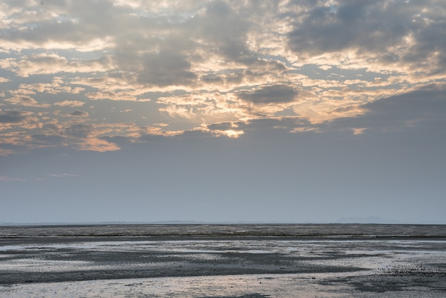 Beautiful low point of view along beach at low tide out to sea with vibrant sunrise sky