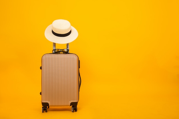 Beautiful luggage and hat isolated on yellow background, accessory travel concept.
