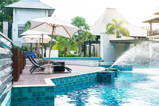 傘と椅子を備えた美しい高級ホテルスイミングプールリゾート