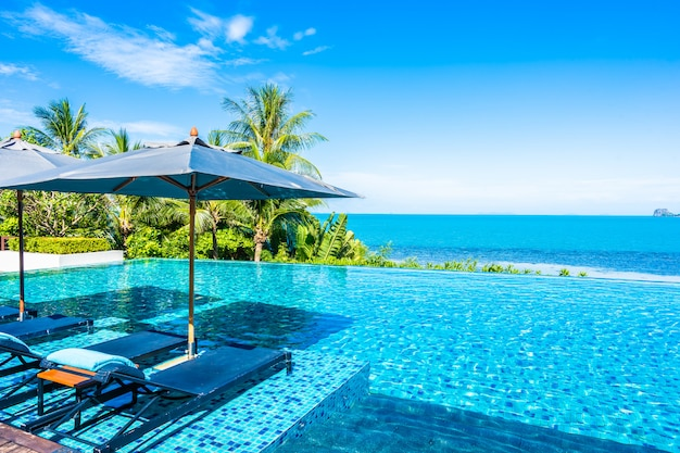 Beautiful luxury outdoor swimming pool in hotel resort with sea ocean around coconut palm tree and white cloud on blue sky