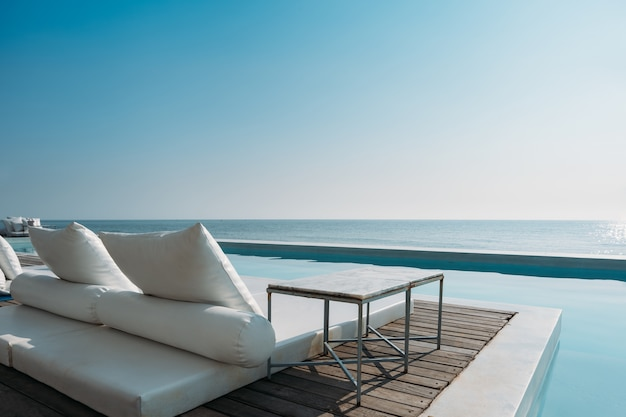 Beautiful luxury swimming pool on sea view and beach chair in hotel resort with blue sky
