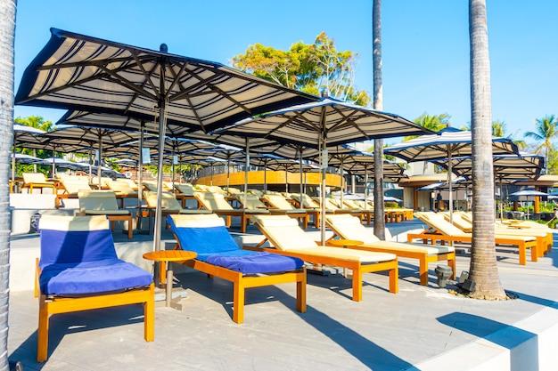 여행 및 휴가 개념 코코넛 야자수와 호텔 및 리조트의 야외 수영장 주변의 아름다운 고급 우산과 의자