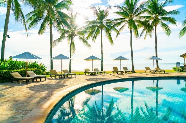 Красивый роскошный зонтик и стул вокруг открытого бассейна в отеле и на курорте с кокосовой пальмой на голубом небе, концепция отпуска и праздника