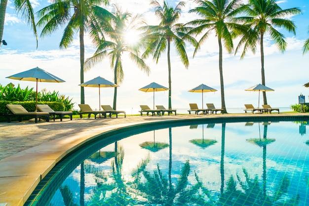 Красивый роскошный зонт и стул вокруг открытого бассейна в отеле и курорте с кокосовой пальмой на голубом небе