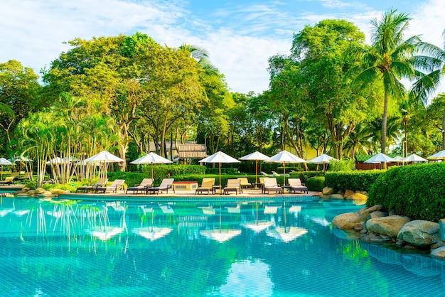 푸른 하늘에 코코넛 야자수와 호텔과 리조트의 야외 수영장 주변의 아름다운 고급 우산과 의자