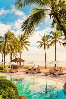 Красивый роскошный зонтик и стул вокруг открытого бассейна в отеле и на курорте с кокосовой пальмой на закате или восходящем небе - концепция праздника и отпуска