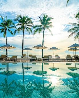휴가 및 휴가 개념-일몰 또는 일출 하늘에 코코넛 야자수와 호텔과 리조트의 야외 수영장 주변의 아름다운 고급 우산과 의자