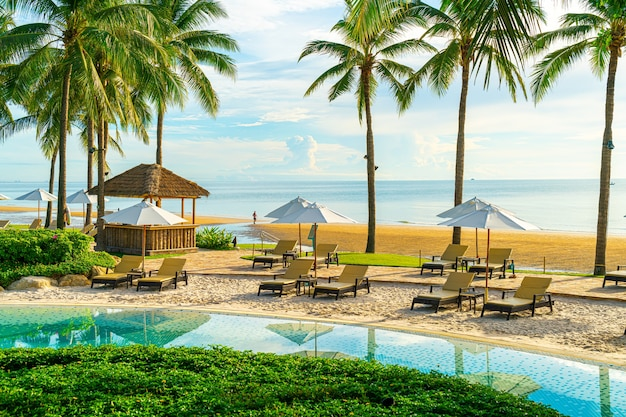일몰 또는 일출 하늘에 코코넛 야자수가 있는 호텔 및 리조트의 야외 수영장 주변에 아름다운 고급 우산과 의자 - 휴일 및 휴가 개념