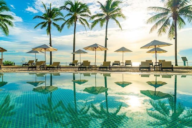 Красивый роскошный зонтик и стул вокруг открытого бассейна в отеле и на курорте с кокосовой пальмой на небе заката или восхода солнца