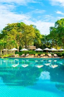 코코넛 야자수가있는 호텔 및 리조트의 야외 수영장 주변의 아름다운 고급 우산과 의자