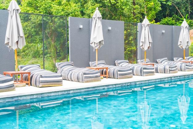 야외 수영장 주변의 아름다운 고급 우산과 의자