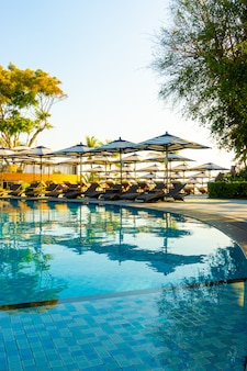 Beautiful luxury umbrella and chair around outdoor swimming pool in hotel and resort with blue sky