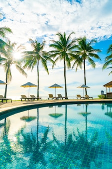 Beautiful luxury umbrella and chair around outdoor swimming pool in hotel and resort with coconut palm tree on blue sky - vacation and holiday concept