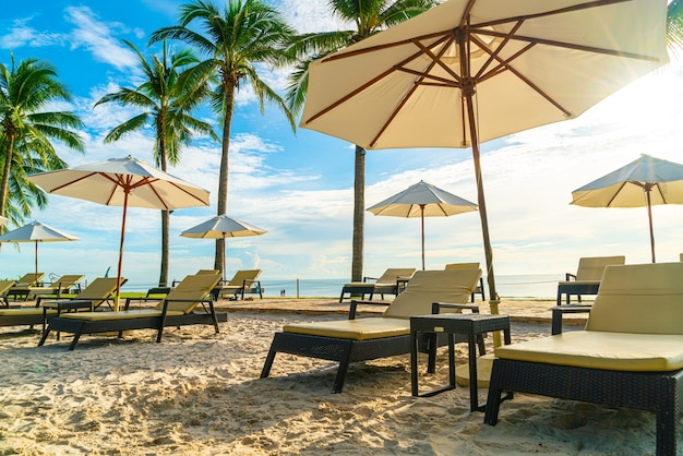 Beautiful luxury umbrella and chair around outdoor swimming pool in hotel and resort with coconut palm tree on sunset  or sunrise sky - holiday and vacation concept