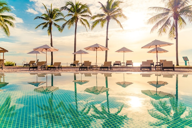 Beautiful luxury umbrella and chair around outdoor swimming pool in hotel and resort with coconut palm tree on sunset  or sunrise sky. holiday and vacation concept